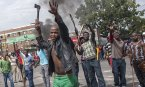 JOHANNESBURG, SOUTH AFRICA - APRIL 17: A group of anti-foreigner violent protesters shout slogans as they hold weapons like hatchets, knifes and some other metal objects, against immigrants during an anti-foreigner protest in Jeppestown suburb of Johannesburg, South Africa on April 17, 2015. Last week, at least 6 people died during the acts of violence and clashes against immigrants in KwaZulu-Natal Province's Durban city. (Photo by Ihsaan Haffejee/Anadolu Agency/Getty Images)